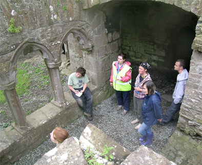 Irish Archaeological Field School examine the stonework in the Abbey cloister.