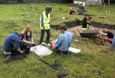 RTÉ film crew examine finds from the site.