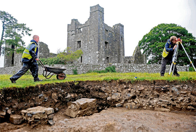 Site supervisor Liam Chambers, with wheelbarrow, and Richard Reid work around two stone pillars uncovered at the excavation site in front of Bective Abbey, Bective, Co Meath, prior to the backfilling of the cuttings (Photo: Barry Cronin).